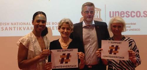 "Personer håller upp unite4heritage loggan. ""We support #unite4heritage"". © UNESCO"