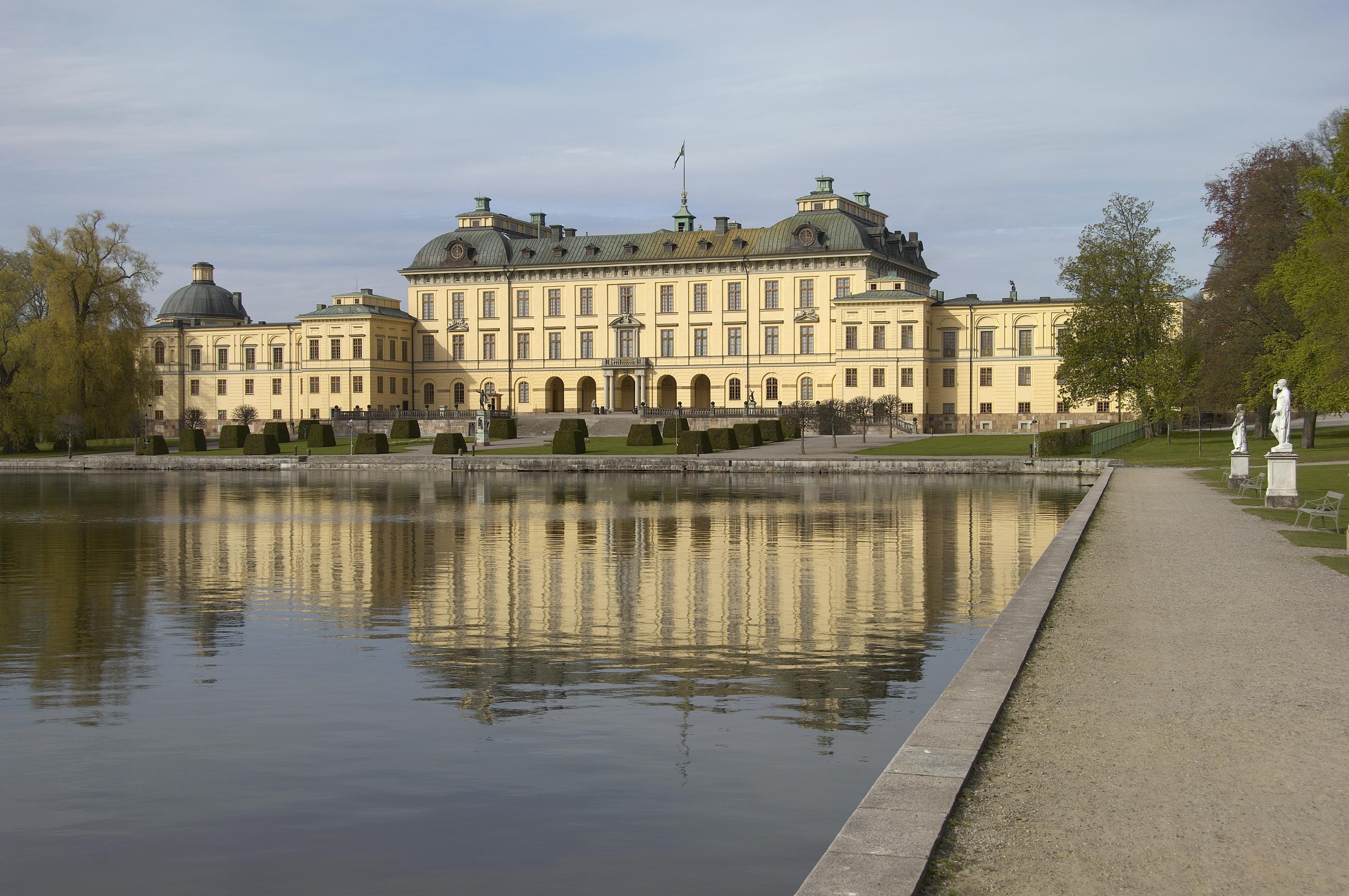 Drottningholms slott sett utifrån med damm i förgrunden.