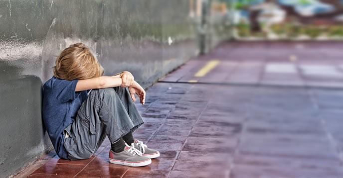 Bild på ett barn som sitter och gråter
